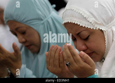 Aceh, Indonesia. 25th Dec, 2014. Indonesian Muslim women participate in mass praying during 10-year commemoration - Stock Photo