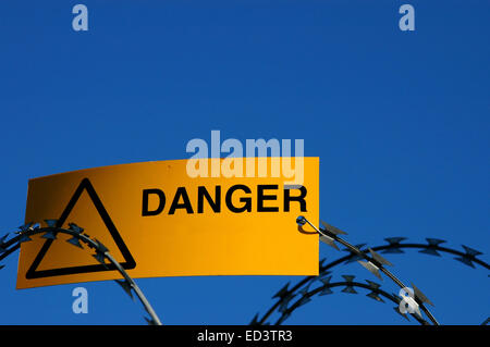 A warning sign on some razor wire - Stock Photo
