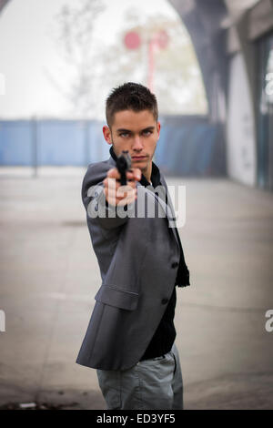 Well dressed handsome young detective or policeman or mobster standing in an urban environment aiming a firearm - Stock Photo