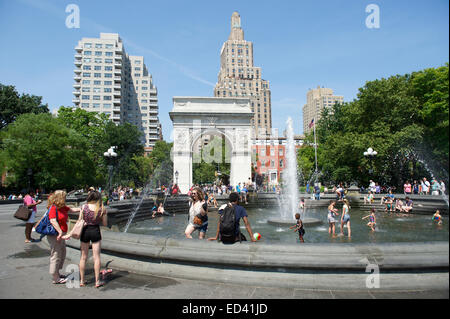 NEW YORK CITY, USA - JUNE 2014: People gather at the fountain in Washington Square Park on a bright summer afternoon. - Stock Photo