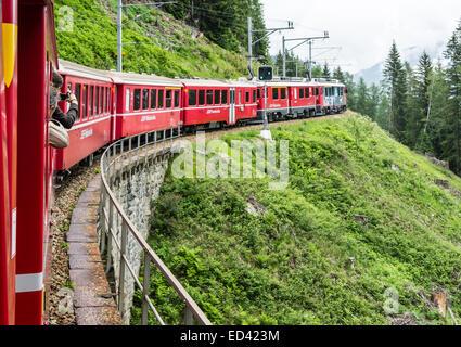Rhatische Bahn train en route to St. Moritz in Switzerland above Poschiavo on the Bernina railway route - Stock Photo