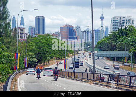 Highway entering the city Kuala Lumpur with view over the Petronas Twin Towers and the Menara tower, Malaysia - Stock Photo