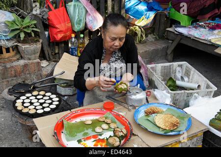 Woman cooking and selling food at open-air market in Luang Prabang, Laos - Stock Photo