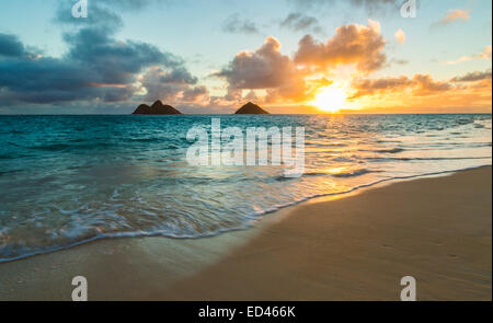 Simple beautiful sunrise over Na Mokulua islands from Lanikai Beach on Oahu, Hawaii - Stock Photo
