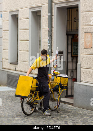 Postman delivering letters from bicycle in the medieval town of Regensburg, Bavaria, Germany - Stock Photo