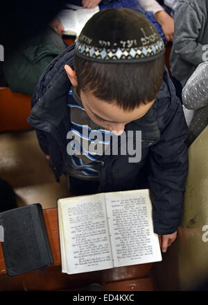 A religious Jewish teenage boy and his prayer book at Chanukkah services at a synagogue in Brooklyn, New York. - Stock Photo