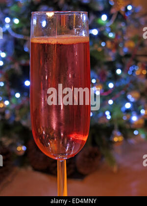 Dangers of festive drinking, one more glass of rose wine at Christmas, in front of tree of decorations - full glass - Stock Photo