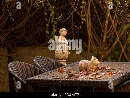 Warm colors of rustic autumn garden table with falling leaves and statue of cat and angel in background - Stock Photo