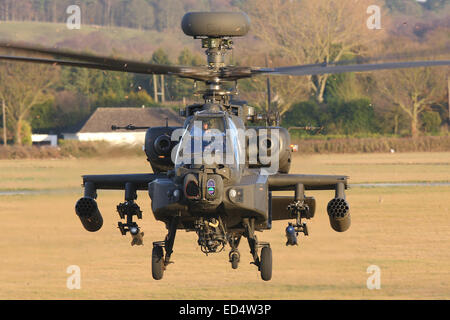 Menacing head on view of British Army Air Corps AAC Agusta Westland Ah-64D Apache attack helicopter in the hover - Stock Photo