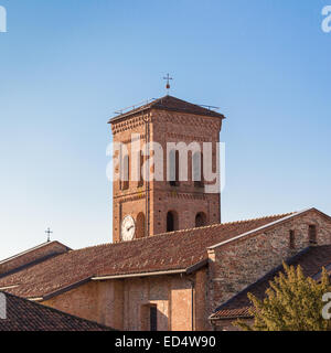Pleasant view of the tower bell of a romanic catholic church in Italy, with roof of the church and beautiful clear - Stock Photo