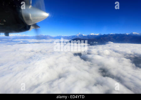 View from a propeller airplane window, flying to Lukla Tenzing Hillary airport with the dramatic Himalaya mountains, - Stock Photo