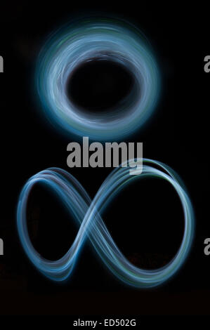 swirling spinning motion and trails traces of moving lights creating patterns vortice joined light rings circle - Stock Photo