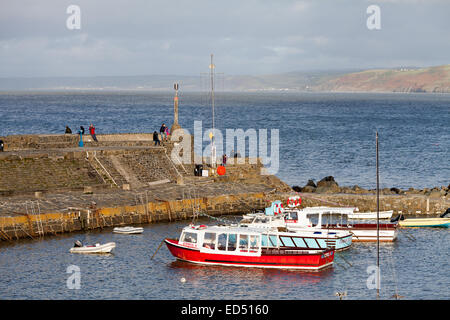 Newquay  harbor in Ceredigion, West Wales.  There are some people on the harbor wall with some moored boats in the - Stock Photo