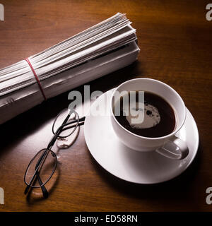 newspaper, glasses and cup of coffee on desk - Stock Photo