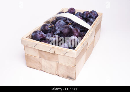 plums in basket on white background - Stock Photo