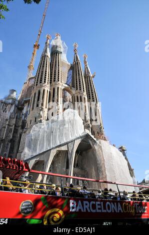 La Sagrada Familia, a major tourist attraction in Barcelona, Catalonia, Spain. A Barcelona city tour bus in front - Stock Photo