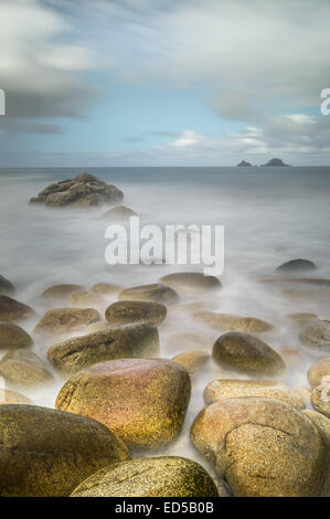 Long exposure as the waves break over the distinctive rocks at Porth Nanven, Cornwall. - Stock Photo