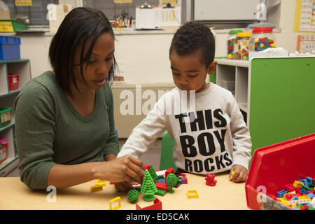 Day Care nursery school on the Lower East Side of Manhattan. Teacher works with child. - Stock Photo