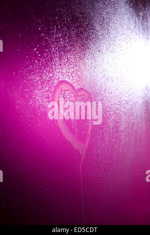 Heart drawn on steamy shower door with a pink / purple light shining behind it - Stock Photo
