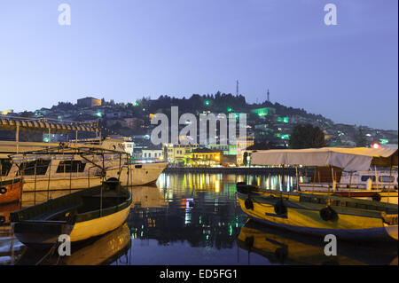 Ohrid lake fishing boats with the view of an old town of Ohrid, Macedonia at night - Stock Photo