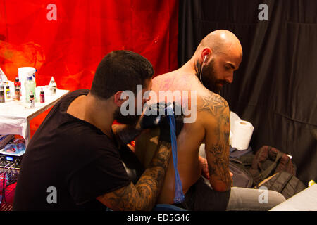 ISTANBUL, TURKEY - SEPTEMBER 20, 2014: Tattoo artist works in Istanbul Tattoo Convention which held in Kadikoy. - Stock Photo