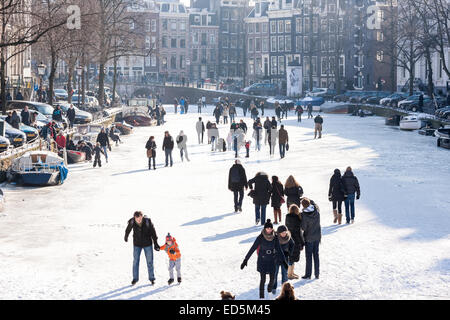 Amsterdam Ice Skating on a frozen Canal in winter. Keizersgracht Canal. - Stock Photo