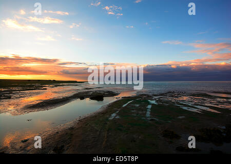 The sun setting over the north Northumberland coast as seen from Lindisfarne (Holy Island) causeway. Northumberland Canvas. Nort Stock Photo