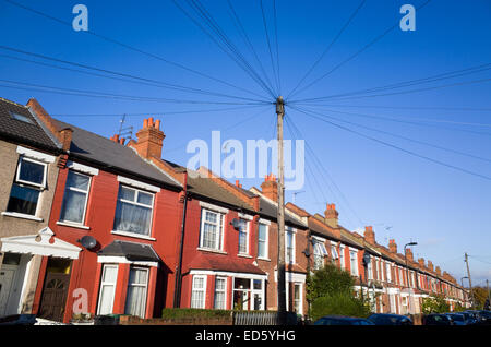 Telephone communication mast with wires running to the terraced houses in residential street, Haringey, London, - Stock Photo