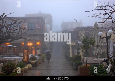 Night falling on misty Arachova, the most popular winter resort in Greece, Mount Parnassos, Viotia., Central Greece. - Stock Photo