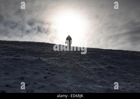 A walker silhouetted against the sun as they stand on a snowy mountain ridge. - Stock Photo
