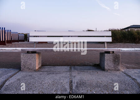 bench on norderney, in background beach chairs - Stock Photo