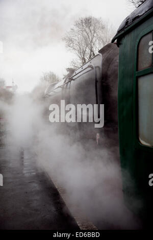 Preserved BR Standard Class 9F 2-10-0 steam locomotive awaits departure amidst clouds of steam in Hampshire - Stock Photo