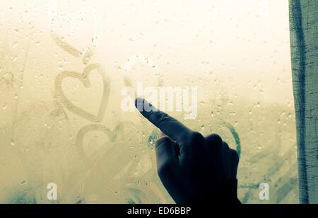 woman drawing heart on wet window - Stock Photo