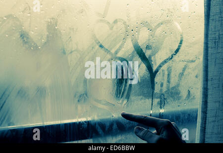 woman drawing heart on wet window - Stock Photo