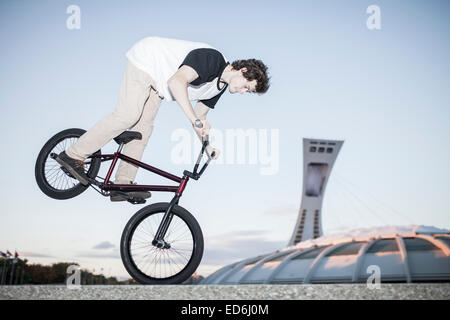 Bmx rider performing a nose manual on concrete block - Stock Photo