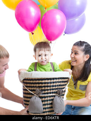 family play at birthday party and playing with son in flight on a makeshift balloon - Stock Photo
