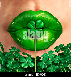 Spring kiss as emerald green lips kissing a four leaf shamrock clover as a st.patrick's day good luck charm celebration - Stock Photo