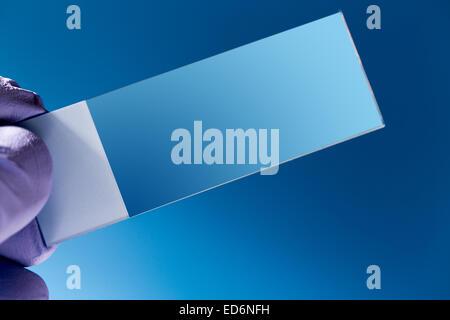 Empty Microscopy slide in hand - Stock Photo