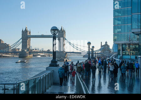 London, UK. 30th December, 2014. Early morning tourists wrapped up from the frost near Tower Bridge. Credit:  Malcolm - Stock Photo