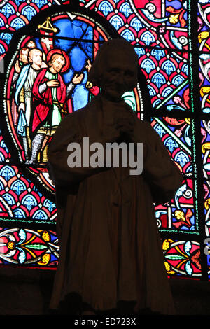 The statue of a priest was put in front of a stained-glass window in Saint-Gatien cathedral in Tours (France). - Stock Photo