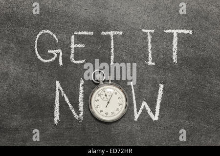 get it now phrase handwritten on chalkboard with vintage precise stopwatch used instead of O - Stock Photo