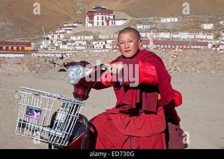 Young monk riding scooter in front of Tibetan monastery Sershu Dzong in the village Sershu / Serxu, Sichuan Province, - Stock Photo
