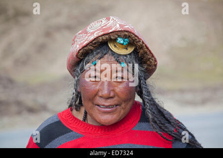 Portrait of Tibetan Khampa woman wearing traditional amber hair piece at Zhuqing, Sichuan Province, China - Stock Photo