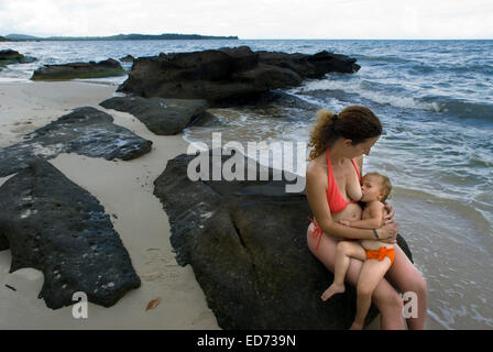 A mother breastfeeds her daughter baby in a virgin beach on the waterfront of Ream National Park. Ream National - Stock Photo
