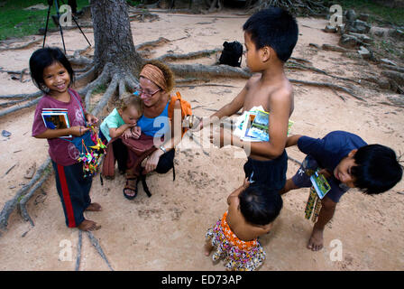 Travel with children's. Boys selling postcards and souvenirs to a mother walking with her daughter.  Ta Som Temple. - Stock Photo