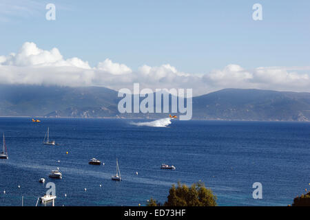 Sea planes scooping up sea water for fire fighting in the Valinco gulf Corsica - Stock Photo