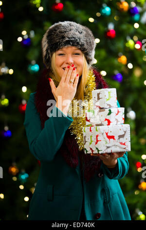 Christmas Xmas: a happy smiling pretty young blonde woman teenage girl wearing a green coat and fur hat with her - Stock Photo
