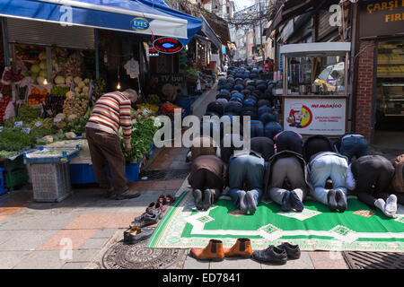 Muslims at Friday prayer on prayer mat by mosque at food and spice market Kadikoy district Asian side Istanbul, - Stock Photo