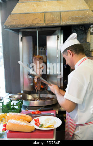 Chef at Ciya Sofrasi Turkish restaurant slicing lamb doner kebab in Kadikoy district Asian side Istanbul, East Turkey - Stock Photo