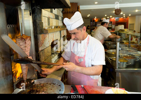 Chef at Ciya Sofrasi Turkish restaurant slicing and serving traditional lamb doner kebab in Kadikoy district on - Stock Photo